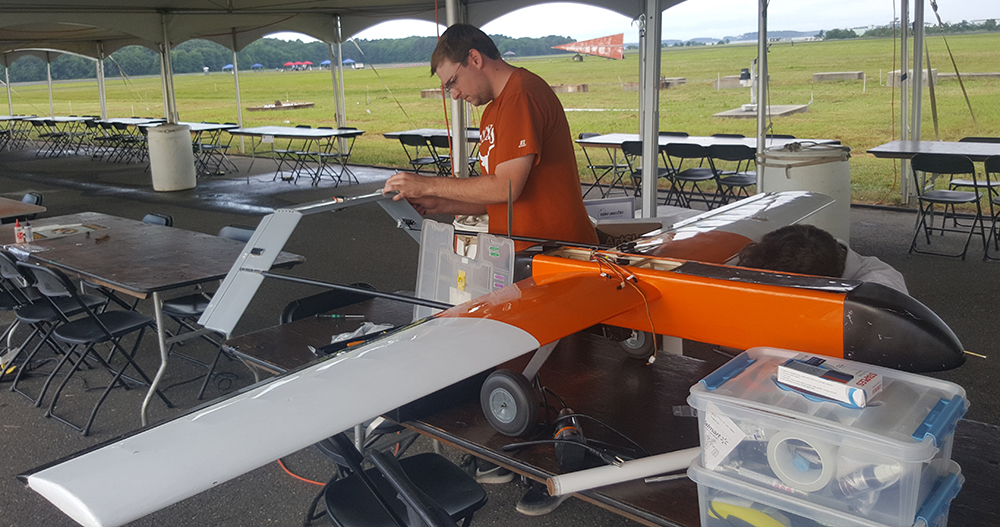photo of student making adjustments to UAV