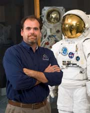 photo of Terry HIll next to space suit