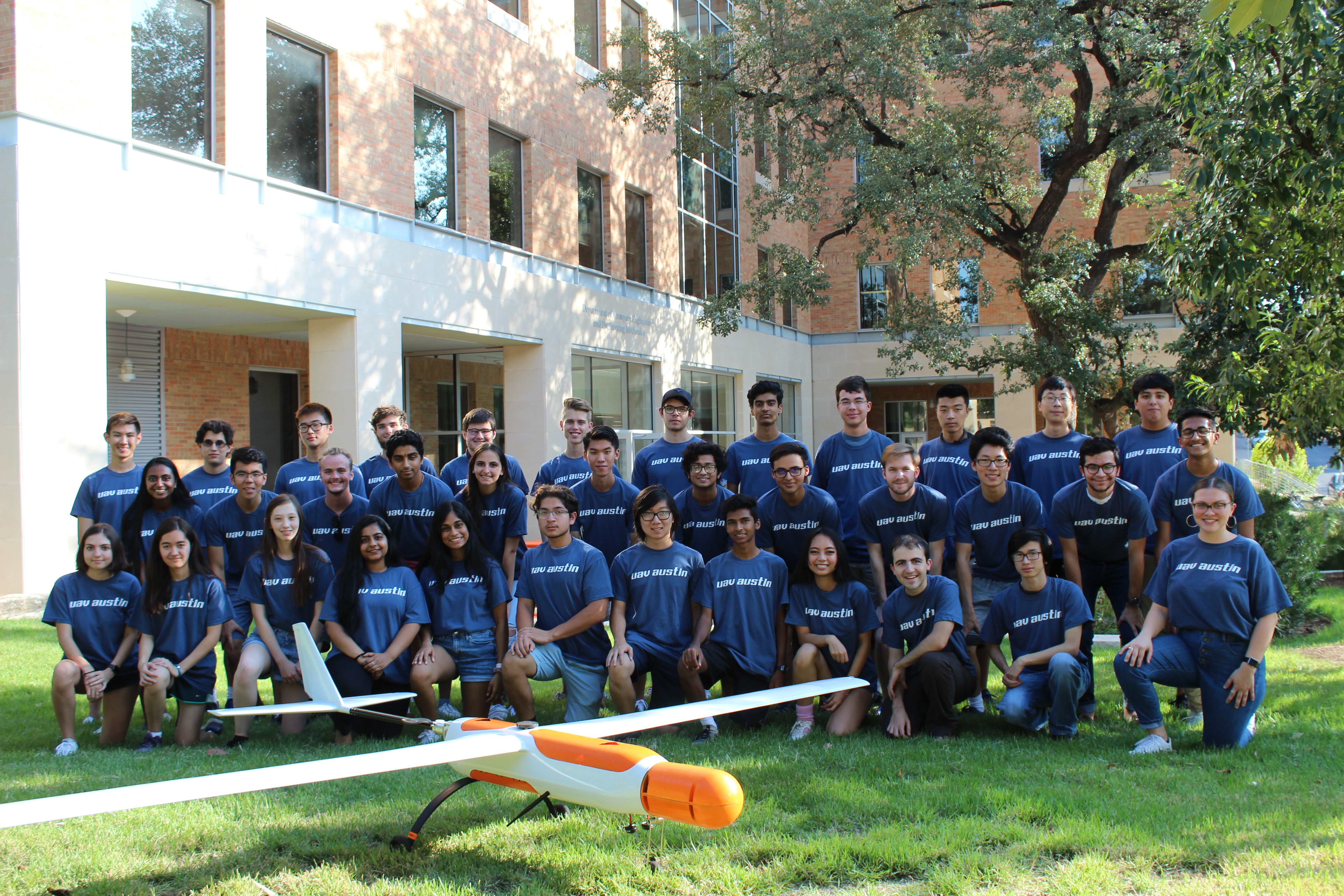 group photo of uav austin members with airplane